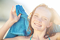Portrait of smiling girl on the beach drying her hair with a beach towel - ZEF003313