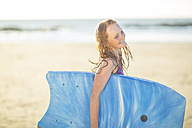 Girl on the beach smiling and holding a boogie board - ZEF003316