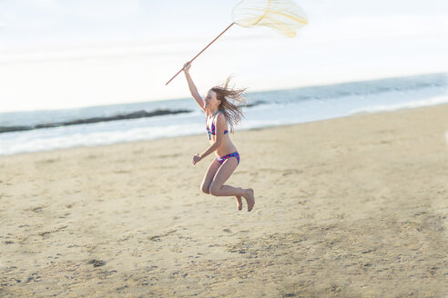 Happy girl on the beach jumping with a butterfly net - ZEF003318
