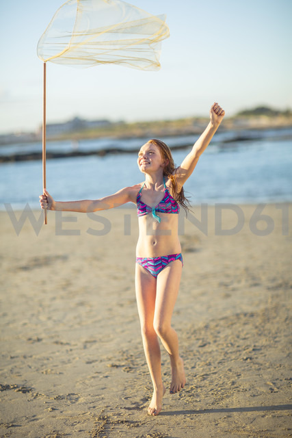 Happy girl on the beach running with a butterfly net - ZEF003319