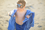 Little boy on the beach dressed up as a superhero with mask and towel - ZEF003411