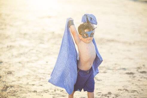 Little boy on the beach dressed up as a superhero with mask and towel - ZEF003414