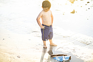 Boy on the beach playing with a toy wooden boat in the water - ZEF003416