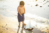 Boy on the beach playing with a toy wooden boat in the water - ZEF003429