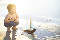 Boy on the beach playing with a toy wooden boat in the water - ZEF003419