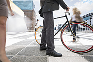Businessman walking with bicycle between a crowd of people in a city - ZEF003972