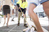 Municipal cleaner sweeping rubbish between a crowd of people in a city - ZEF003975