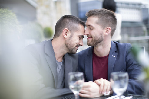 Gay couple sharing an intimate moment at a restaurant - ZEF002900