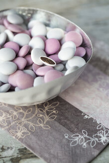 Bowl of white and pink chocolate beans on paper napkin - SARF001213
