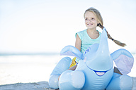 Smiling girl on beach sitting on an inflatable elephant - ZEF003324