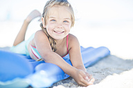 Smiling girl on beach lying on a lilo - ZEF003347
