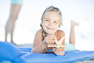 Smiling girl on beach lying on a lilo holding a starfish - ZEF003348