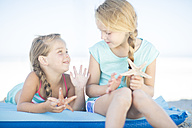 Two girls on beach on a lilo with starfish - ZEF003354