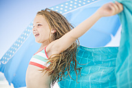 Smiling girl on beach drying off with a beach towel - ZEF003367