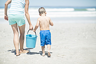 Mother and son on beach walking with a bucket - ZEF003382