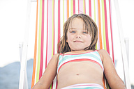 Smiling girl on beach relaxing on a beach chair - ZEF003388