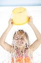 Girl on beach splashing herself with a bucket of water - ZEF003398