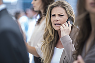 Annoyed businesswoman on cell phone in busy city - ZEF003236