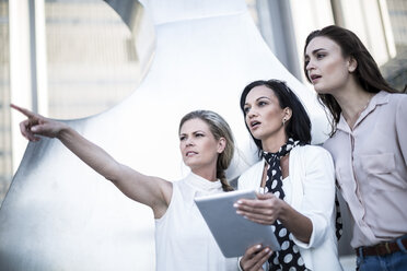 Three women with digital tablet in the city - ZEF003262