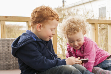 Little boy and girl looking at cell phone - NNF000302