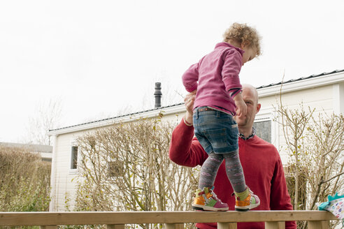 Father helping little daughter balancing on balcony - NNF000304
