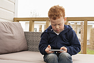 Little boy looking at cell phone - NNF000305