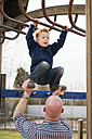 Father helping son on playground climbing on jungle gym - NNF000306