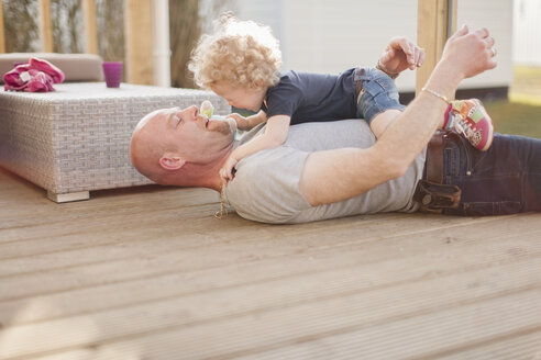 Father playing with little daughter on terrace - NNF000317