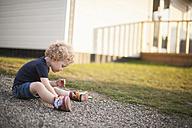 Little girl sitting on gravel path - NNF000324