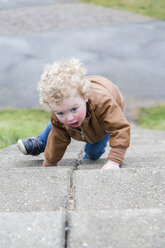 Little girl crawling up stairs - NNF000331