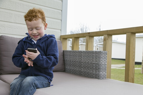 Smiling little boy looking at cell phone - NNF000332