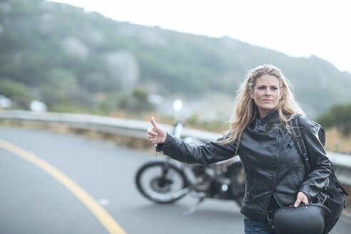 Woman hitchhiking next to motorcycle on the road - ZEF003601