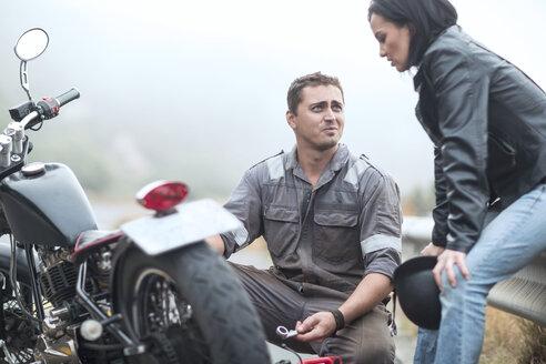 Motorcycle technician helping stranded biker with broken bike - ZEF003604