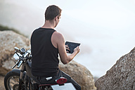 South Africa, Cape Town, motorcyclist at the coast taking pictures with digital tablet - ZEF003611