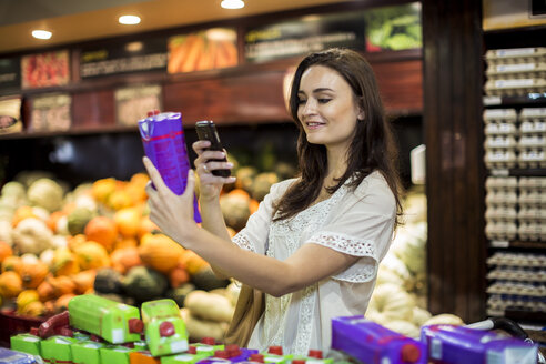 Woman at supermarket scanning prices with her smart phone - ZEF004183