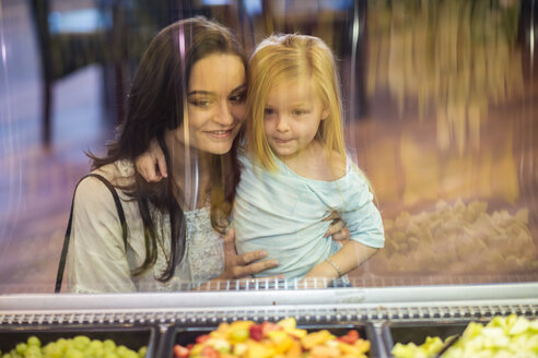 Mother and daughter looking at fruit salad in supermarket - ZEF004195