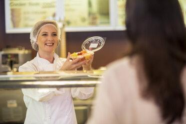 Shop assistant packing fruit salad for customer - ZEF004198