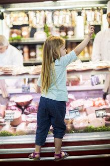 Little girl standing on counter of butchery - ZEF004201