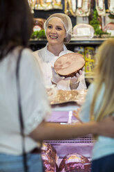 Customer with daughter buying ham at butchery - ZEF004202