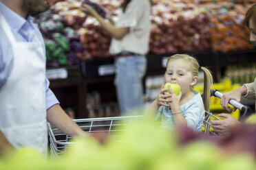 Girl sitting in shopping trolley eating apple - ZEF004205