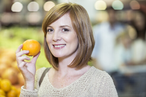 Young woman in supermarket holding orange - ZEF004208