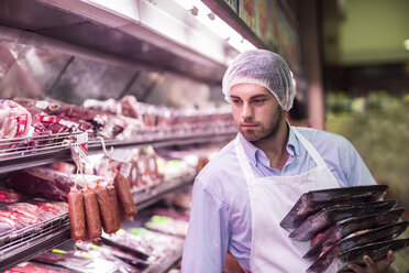 Butcher filling shelf with packaged meat - ZEF004213