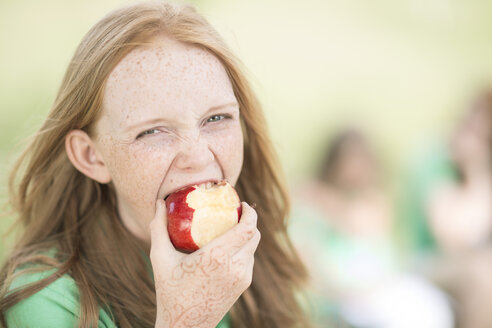 Portrait of girl with red hair eating an apple - ZEF004383