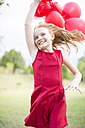 Portrait of running girl with red balloons wearing red dress - ZEF004390