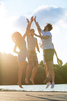 Four friends high fiving at a lake in backlight - WESTF020719