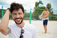 Smiling young man on beach volleyball field - WESTF020724