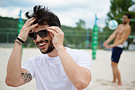 Smiling young man on beach volleyball field - WESTF020726