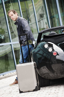 Young man with rolling suitcase leaning at his sports car - HHF005022