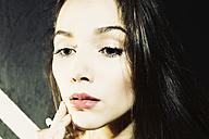 Close-up of young woman applying makeup - MEM000604