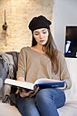 Young woman on sofa reading coffee-table book - MEMF000616
